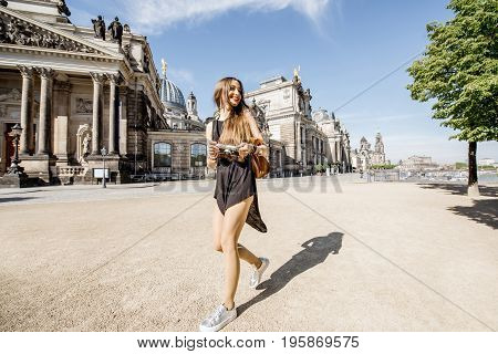 Young and happy woman touirst walking in front of the old university building in Dresden, Germany