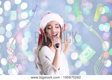 Young woman with headphones singing song on blurred lights background. Christmas and New Year music