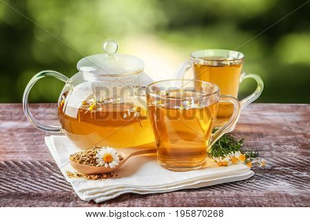 Hot chamomile tea in cups and pot with flowers on wooden table outdoor