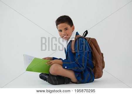 Portrait of schoolboy holding book against white background