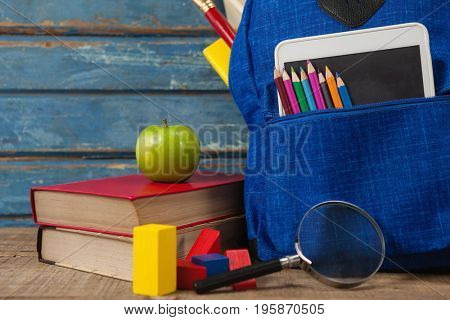 Close-up of school supplies, apple, digital tablet and magnifying glass on wooden table
