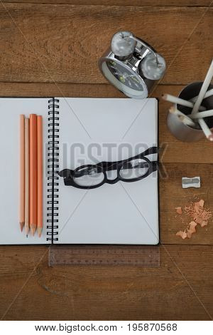 Overhead view of alarm clock, book, pencil, scale, spectacles and sharpener on wooden table