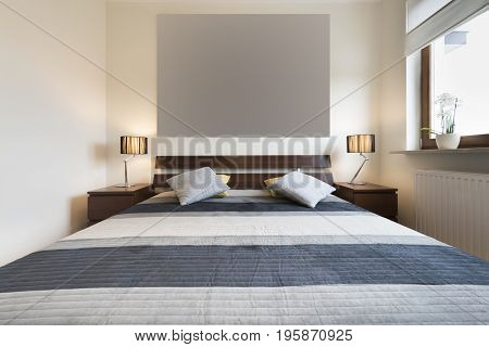 Modern bedroom in beige finishing and queens bed