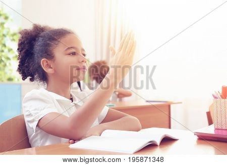 African-American schoolgirl sitting at table in classroom