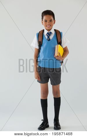 Portrait of schoolboy in school uniform with school bag on white background