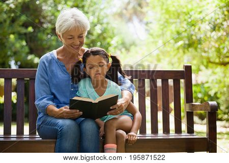 Grandmother reading novel to granddaughter sitting on wooden bench at garden