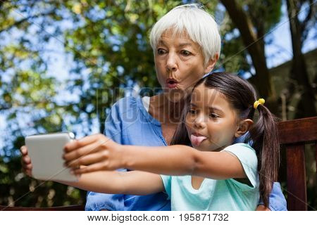 Grandmother and granddaughter making face while taking selfie sitting on bench at backyard
