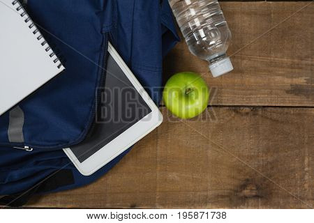 Close-up of schoolbag, apple, water bottle, book and digital table on wooden table
