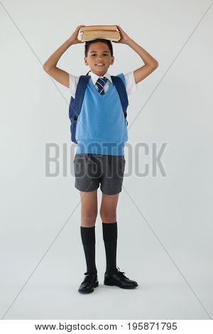 Portrait of schoolboy holding books on his head against white background