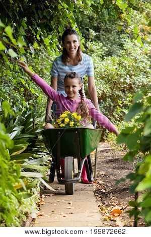 Woman pushing girl sitting with outstretched in wheelbarrow on footpath amidst plants at garden