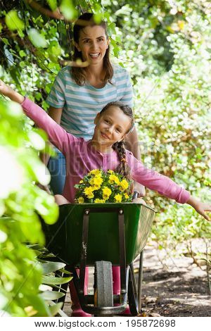 Girl enjoying with arms outstretched while smiling mother pushing wheelbarrow on footpath by plants
