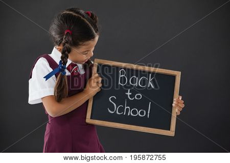 Schoolgirl holding slate with text against blackboard in classroom