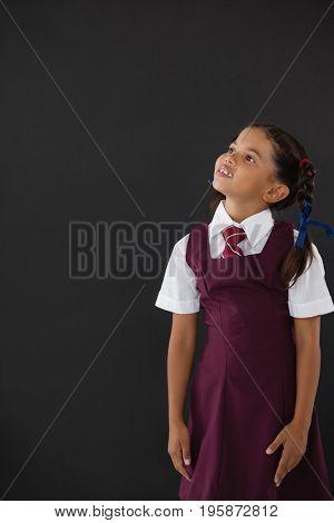 Thoughtful schoolgirl standing against blackboard in classroom