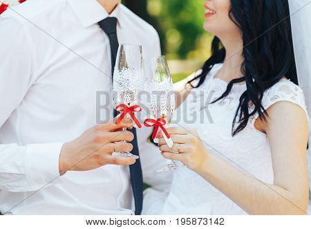 The bride and the groom hold their wedding glasses with champagne