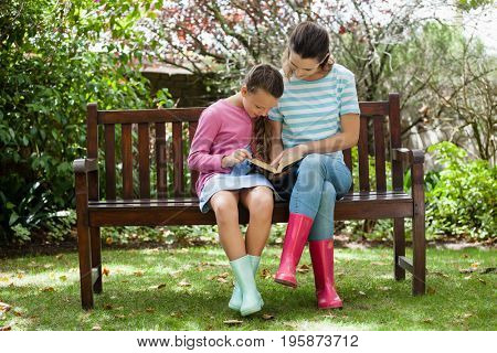 Mother and daughter reading novel while sitting on wooden bench at backyard
