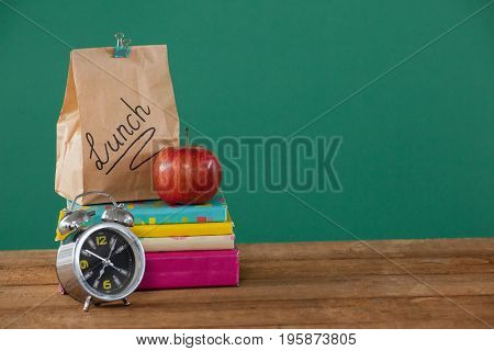 Alarm clock, lunch paper bag and apple on books stack against green background