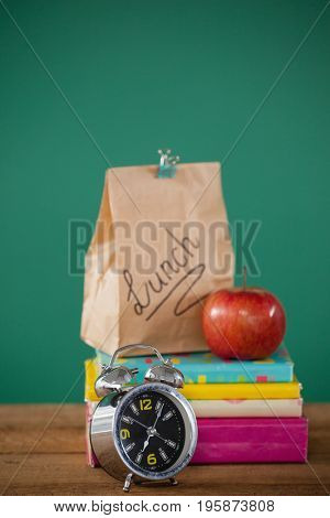 Alarm clock and lunch paper bag with apple on books stack against green background
