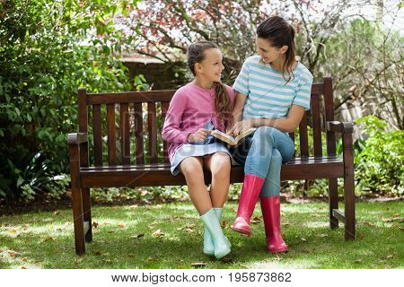 Cheerful mother and daughter reading novel while sitting on wooden bench at backyard