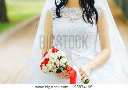 Bride in white dress holds wedding bouquet in hands