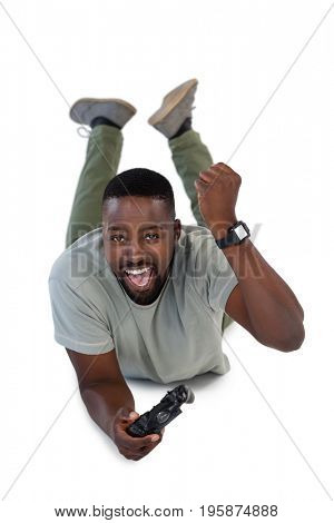 Excited man playing video games against white background