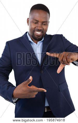 Smiling businessman forming a finger frame against white background