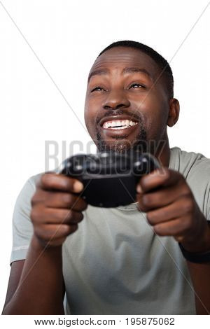 Close-up of smiling man playing video game against white background