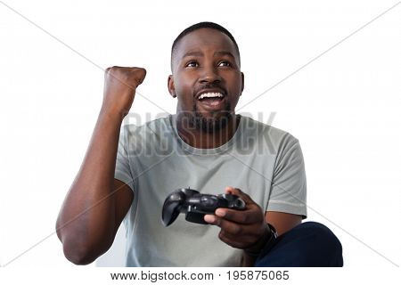 Excited man playing video game against white background
