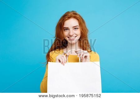 Close up Portrait young beautiful attractive redhair girl smiling with white shopping bag. Blue Pastel Background.