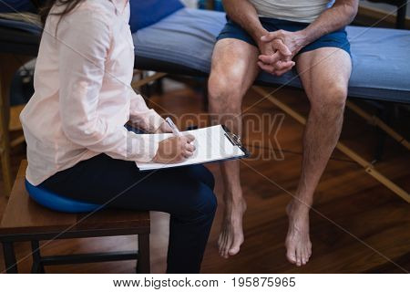 High angle view female therapist writing on clipboard while sitting by senior male patient at hospital ward