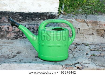 Watering can on stone steps in the garden