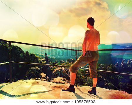 Film Effect. Naked Hiker On The Peak Of Rock Watching Into Landscape.