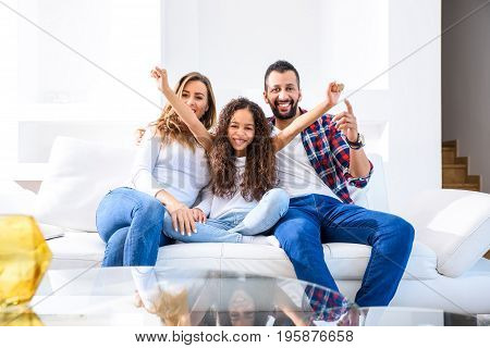 Young parents siting on the couch with their daughter who is feeling happy and celebrating