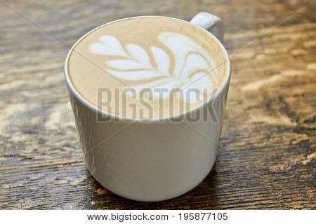 Latte cup on wood. Flower coffee foam art.