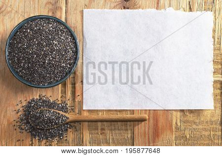 Chia seeds in bowl with spoon and paper for text on the old wooden table top view