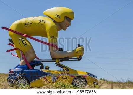 Saint-Quentin-FallavierFrance - July 16 2016: LCL traditional cyclist mascot during the passing of Publicity Caravan in a wheat plain in the stage 14 of Tour de France 2016. LCL was the largest bank in France and sponsored continuosly the TDF during more