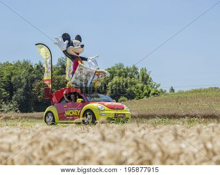 Saint-Quentin-Fallavier France - July 16 2016: Le Journal du Mickey car during the passing of Publicity Caravan in a wheat plain in the stage 14 of Tour de France 2016. Le Journal du Mickey is a French weekly comics magazine presenting adventures of Micke
