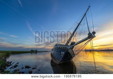 Scenic sunset at a stranded sailing boat near Lemmer, the Netherlands. It was left behind by its unknown owner forcing local authorities to pull it away after a few weeks.