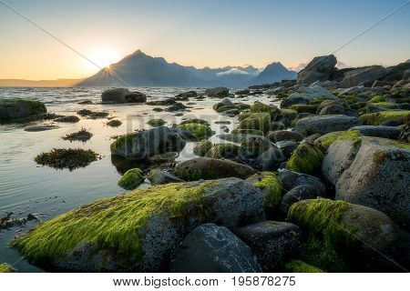 Nice sunset across rocky Elgol beach on the Scottish Isle of Skye with a view towards the Black Cuillin mountain range.