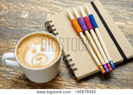 Coffee, pencils and notebook. Latte foam art. Is caffeine good for studying.