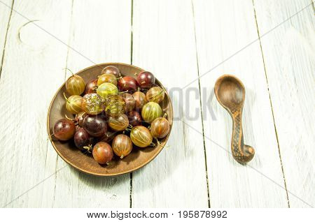 Sliced Berry Gooseberries. Multicolored Berries Of Gooseberries On A Plate. Clay Dishes.
