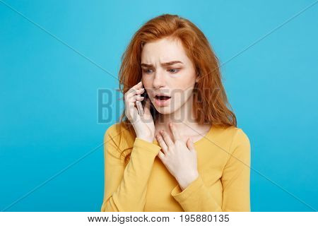 Portrait of a surprised confused woman in yellow casual calling mobile phone isolated over blue background