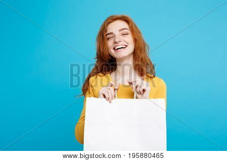 Shopping Concept - Close up Portrait young beautiful attractive redhair girl smiling looking at camera with white shopping bag. Blue Pastel Background. Copy space.