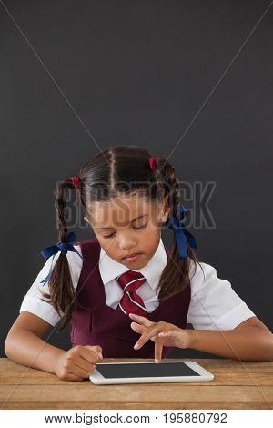 Schoolgirl using digital tablet against blackboard in classroom
