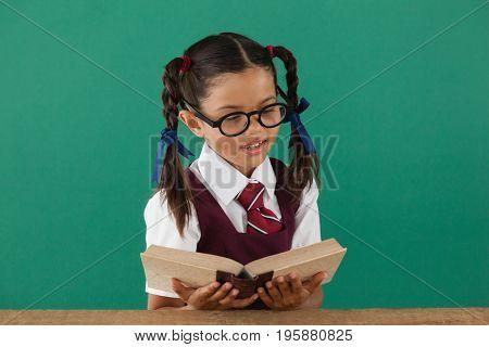 Schoolgirl reading book against chalkboard in classroom
