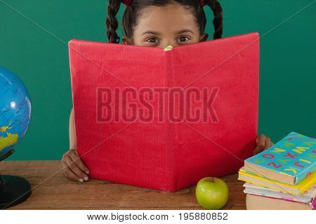 Portrait of schoolgirl hiding behind a book against green background