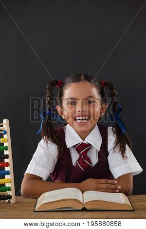 Portrait of schoolgirl reading a book against chalkboard