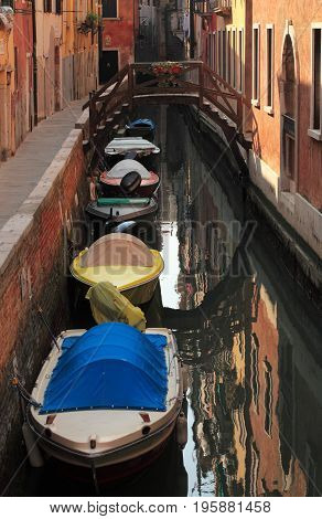 Engine powered boats parked near the walls on a narrow Venetian canal.
