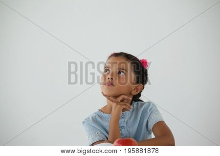 Thoughtful young girl sitting against white background
