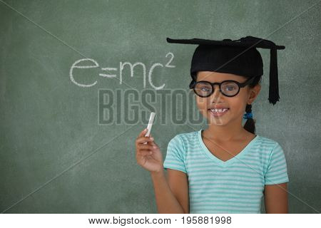 Young girl with graduation hat holding chalk against chalk board