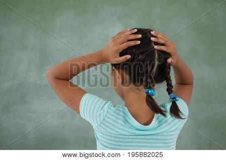Rear view of young girl holding her head